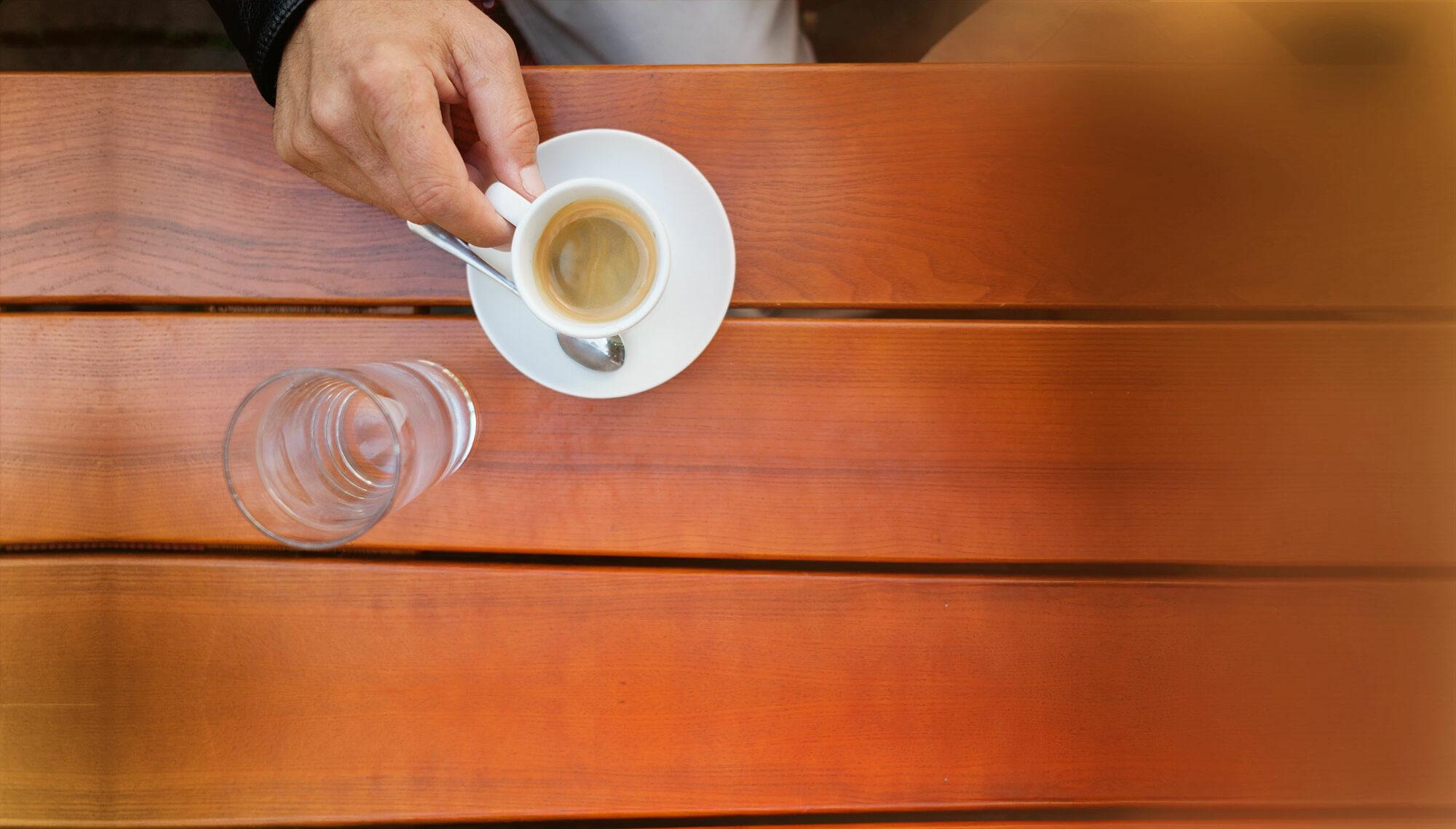 Mag. Thomas Plattner, Geschäftsführer von Austrotax. Nur seine Hand zu sehen, mit einer vollen Kaffeetasse.