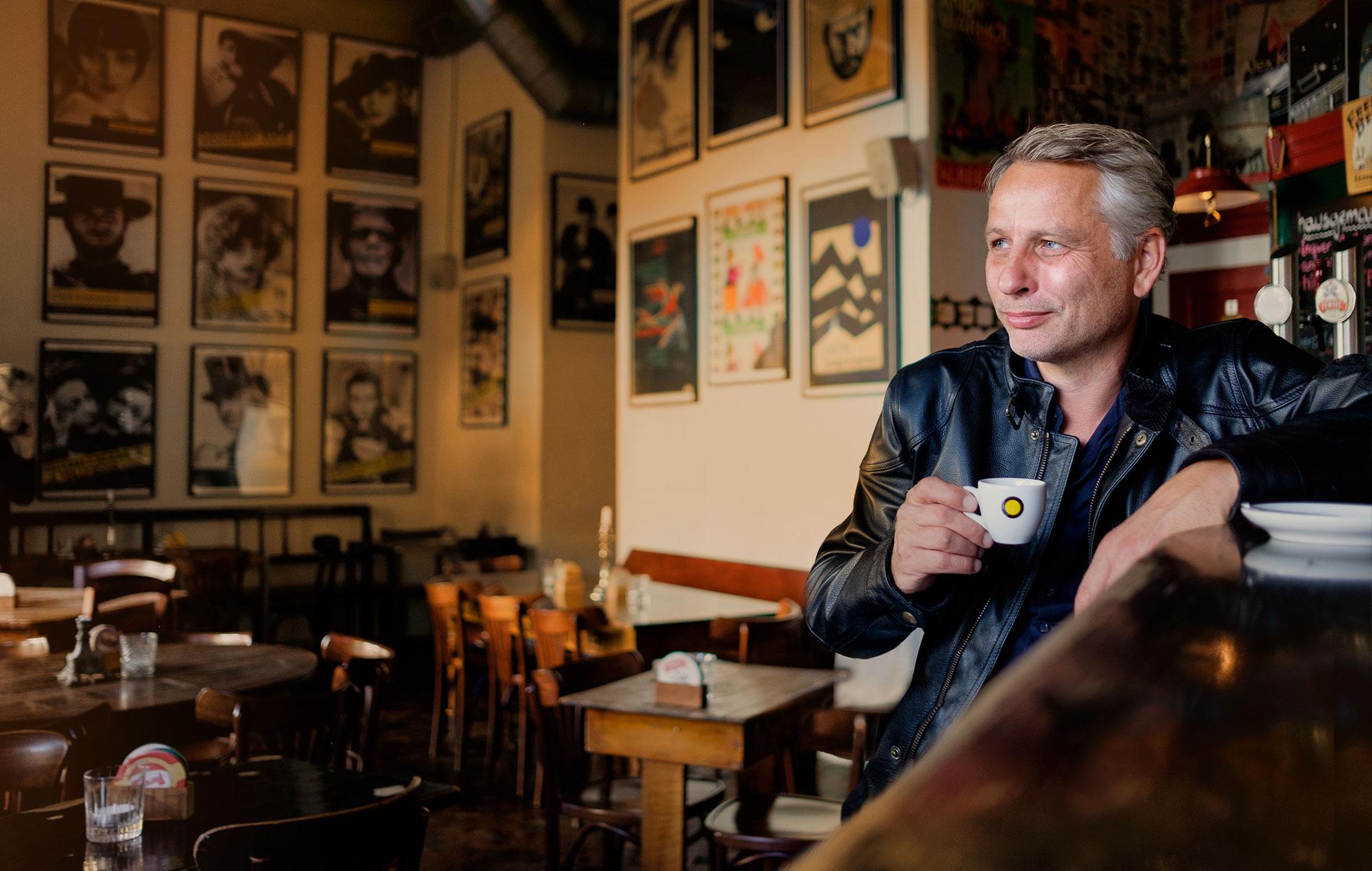 Mag. Thomas Plattner, Geschäftsführer von Austrotax. Zu sehen in einem Café mit einer Kaffeetasse in der Hand.