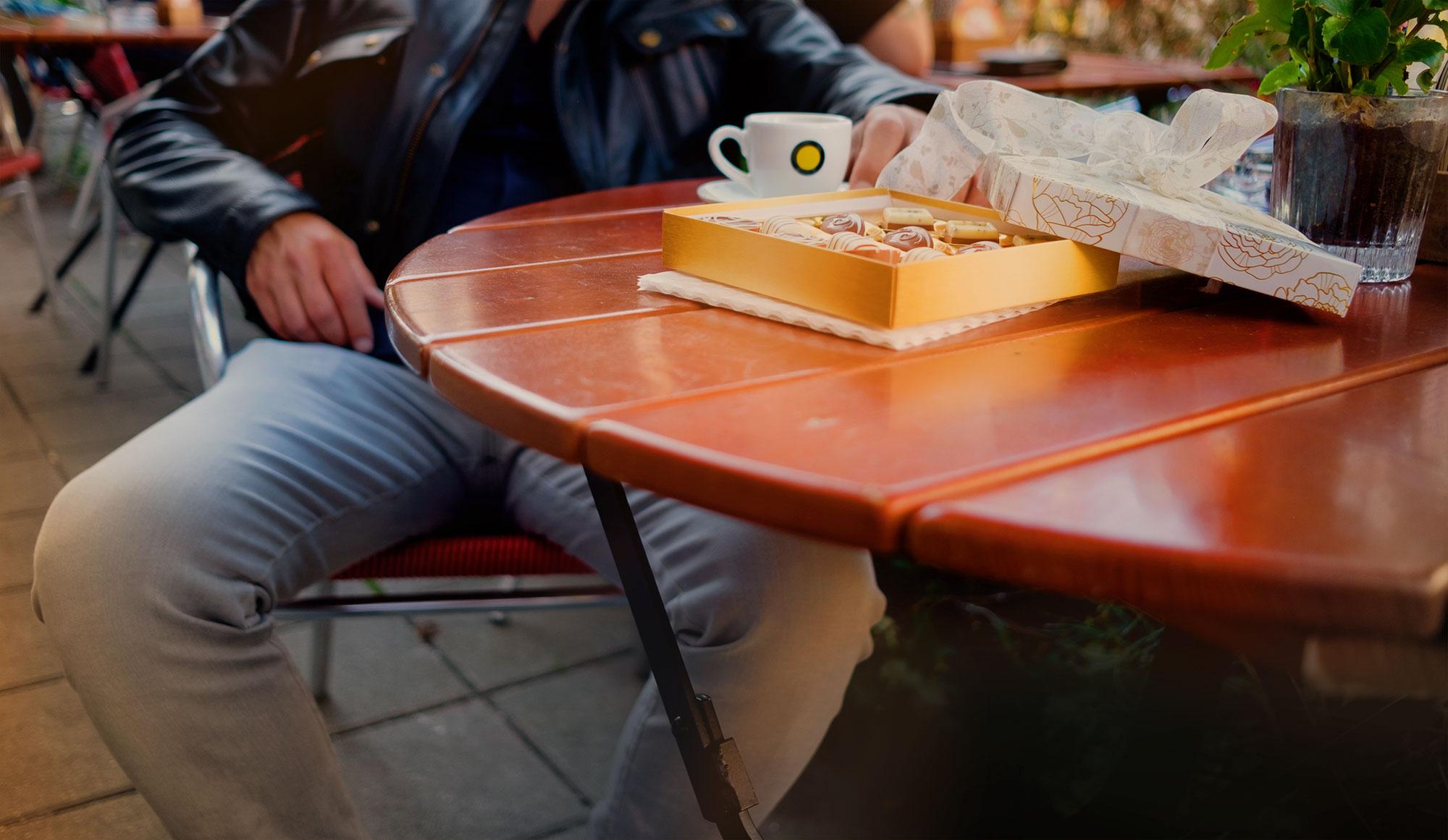 Pralinenschachtel und Kaffetasse auf einem Tisch.